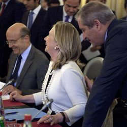 From left, France's Foreign Minister Alain Juppe, Secretary of State Hillary Rodham Clinton, and an unidentified participant speak before meeting on Syria, Thursday, April 19, 2012, in Paris.