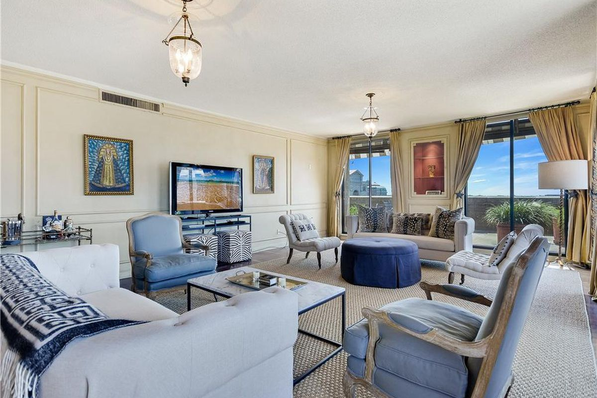 Large condo living room with big curtained windows and views