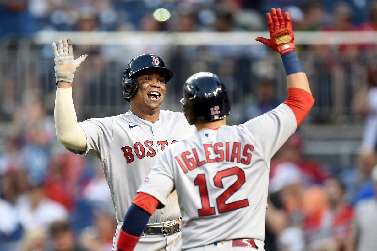 Rafael Devers #11 of the Boston Red Sox celebrates with Jose Iglesias #12 after hitting the game winning two-run home run in the ninth inning against the Washington Nationals at Nationals Park on October 03, 2021 in Washington, DC.