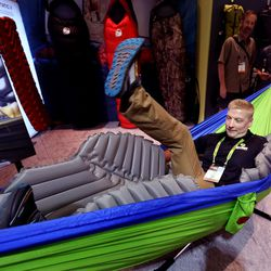Andrew Kase slips into a hammock with a Klymit V sleeping pad at the Outdoor Retailer Summer Market at the Salt Palace Convention Center in Salt Lake City on Wednesday, Aug. 3, 2016. Klymit is based out of Centerville.