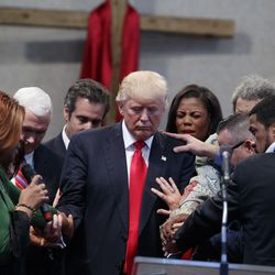 People lay hands on Republican presidential candidate Donald Trump as they pray during a visit to the Pastors Leadership Conference at New Spirit Revival Center, Wednesday, Sept. 21, 2016, in Cleveland, Ohio.