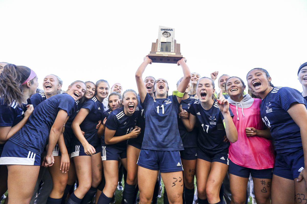 Skyline's Ani Jensen (11) hoists the team's state championship trophy into the air as they celebrate after winning the 5A girls state soccer match 2-1 over Bonneville at Rio Tinto Stadium in Sandy on Friday, Oct. 25, 2019.