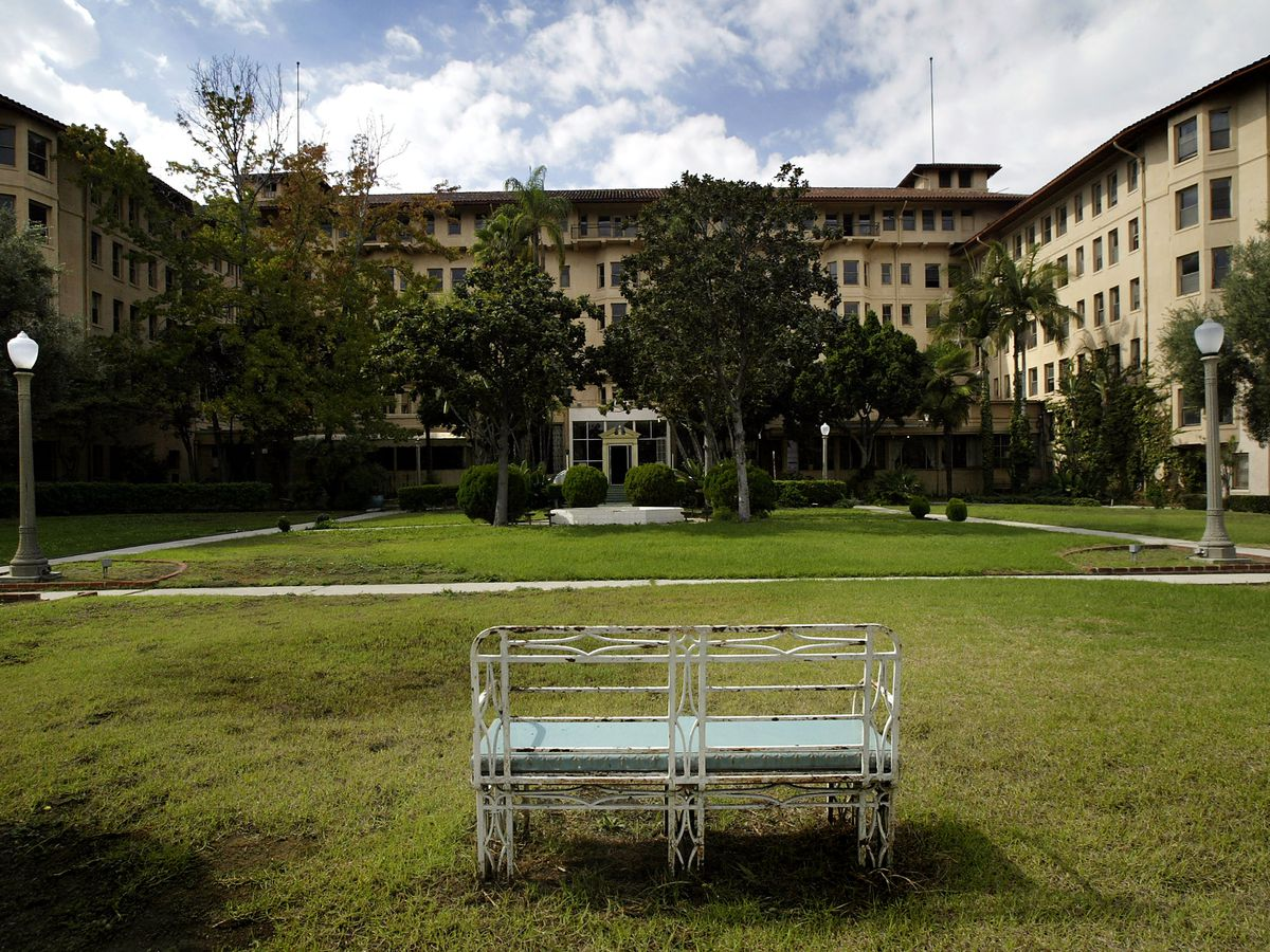 A large hotel building with a lawn in front of it.