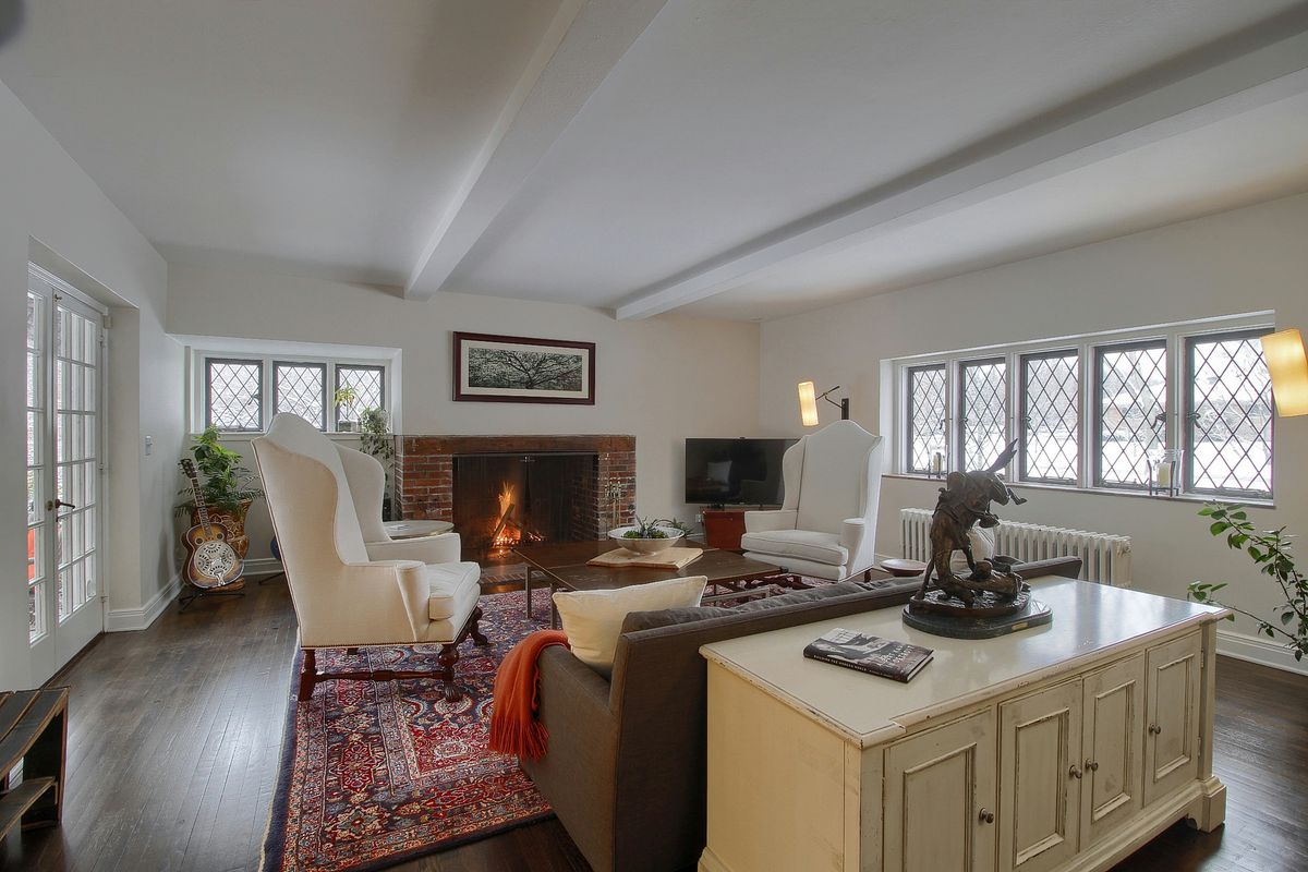 A large room with two chairs and a sofa around a brick fireplace. There's french doors to one side and leaded glass windows on the other.