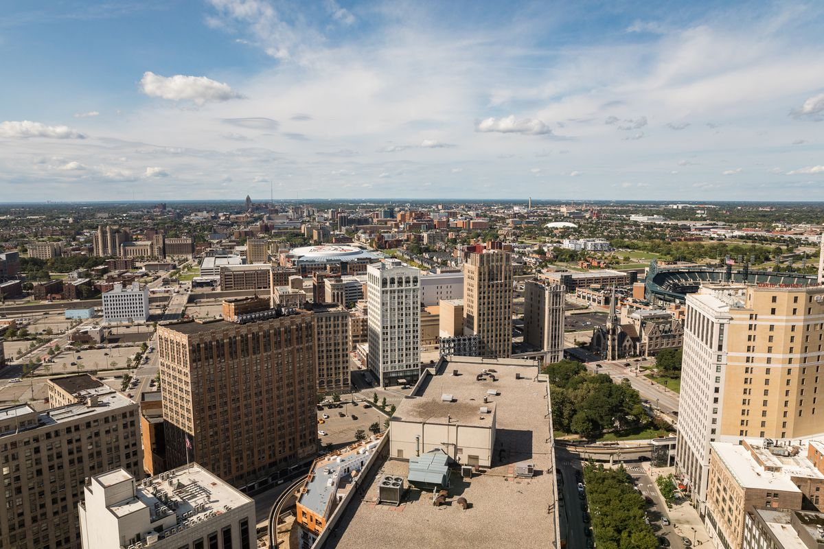An aerial view of downtown Detroit.  There are many tall buildings and trees.