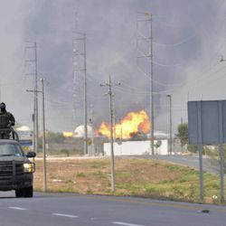 A Mexican army vehicle patrols on a road as fire and smoke rise from a gas pipeline distribution center in Reynosa, Mexico near Mexico's border with the United States, Tuesday Sept. 18, 2012. Mexico's state-owned oil company, Petroleos Mexicanos, also known as Pemex said the fire had been extinguished and the pipeline had been shut off but ten people were killed during the incident.