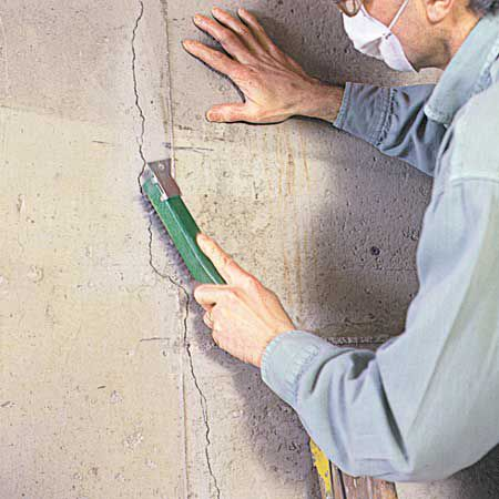 Man Using Wire Brush to Clean Crack in Concrete