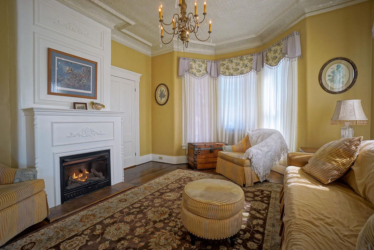 A living room has a white fireplace, yellow walls, a chandelier, and yellow couches.