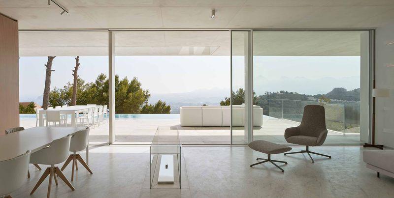 Living room with concrete floor and open doors to patio