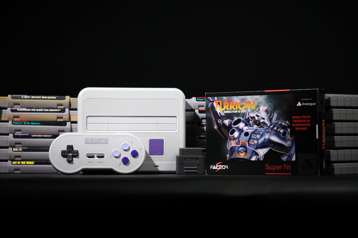classic Analogue Super NT console and 8Bitdo gamepad with Super Turrican: Director's Cut box in front of stacks of SNES cartridges