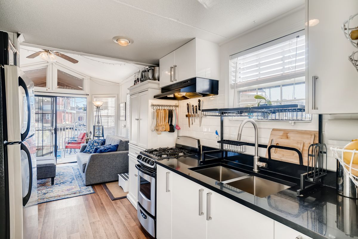 A galley kitchen has black countertops, white cabinets, and a window above the sink.