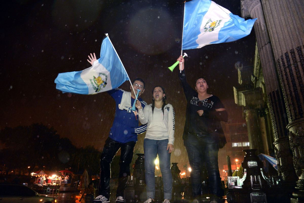 Protesters in Guatemala City wave flags in celebration after the Guatemalan Congress's unanimous vote to strip immunity from President Perez Molina.