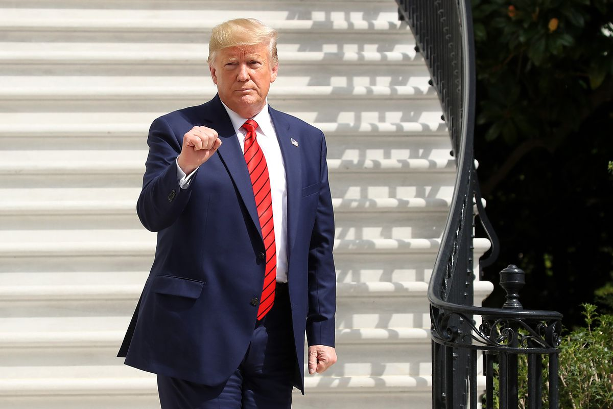 President Donald Trump standing at the base of a flight of steps outside the White House and making a fist gesture.