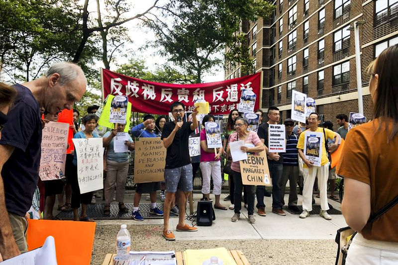 Zishun Ning, an organizer with Chinese Staff Workers Association, holds the megaphone during a rally protesting luxury development in the Two Bridges neighborhood and displacement within Chinatown and Lower East Side.