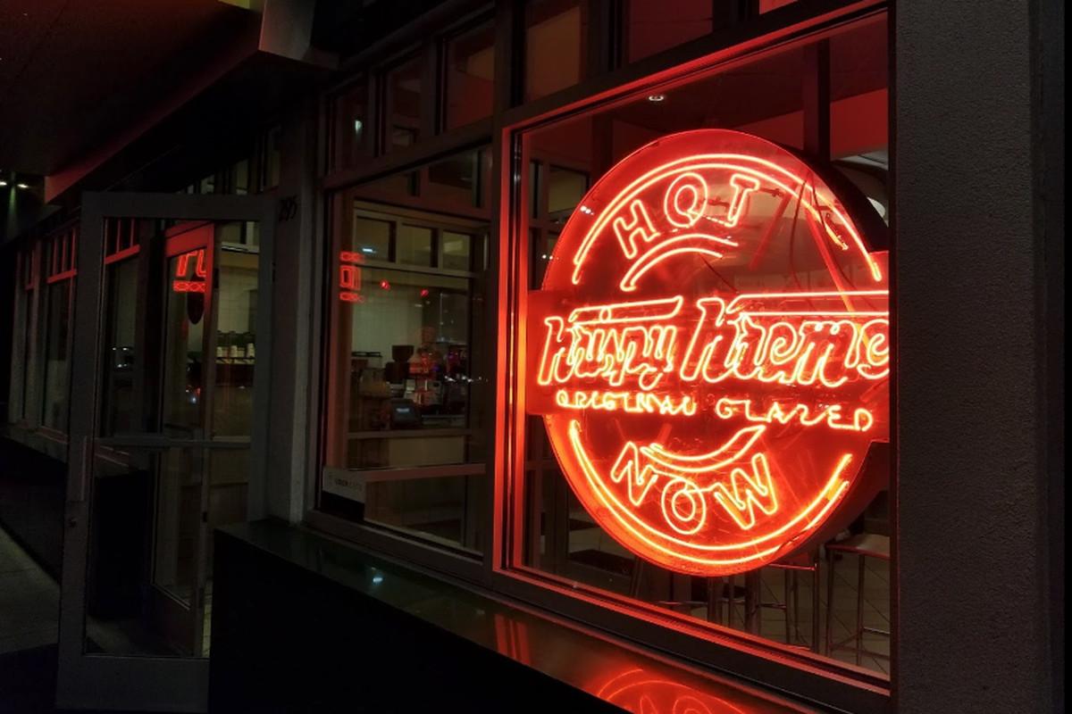 A neon red sign aglow at the Krispy Kreme doughnuts on Ponce de Leon Avenue in Atlanta stating HOT Krispy Kreme Glazed NOW