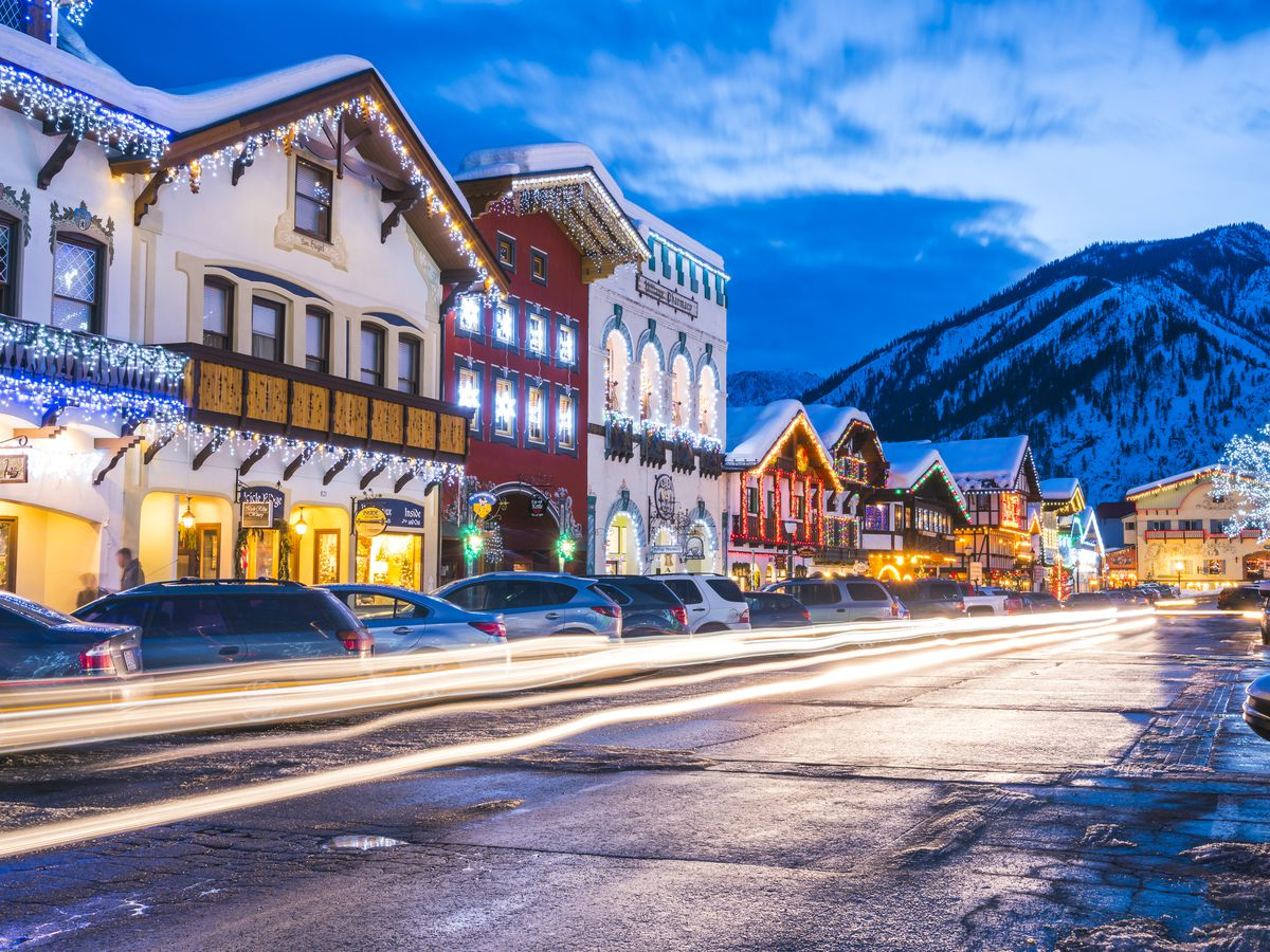 A snowy road lined with Bavarian-style buildings decorated with string lights. There's a snowy hill in the background.