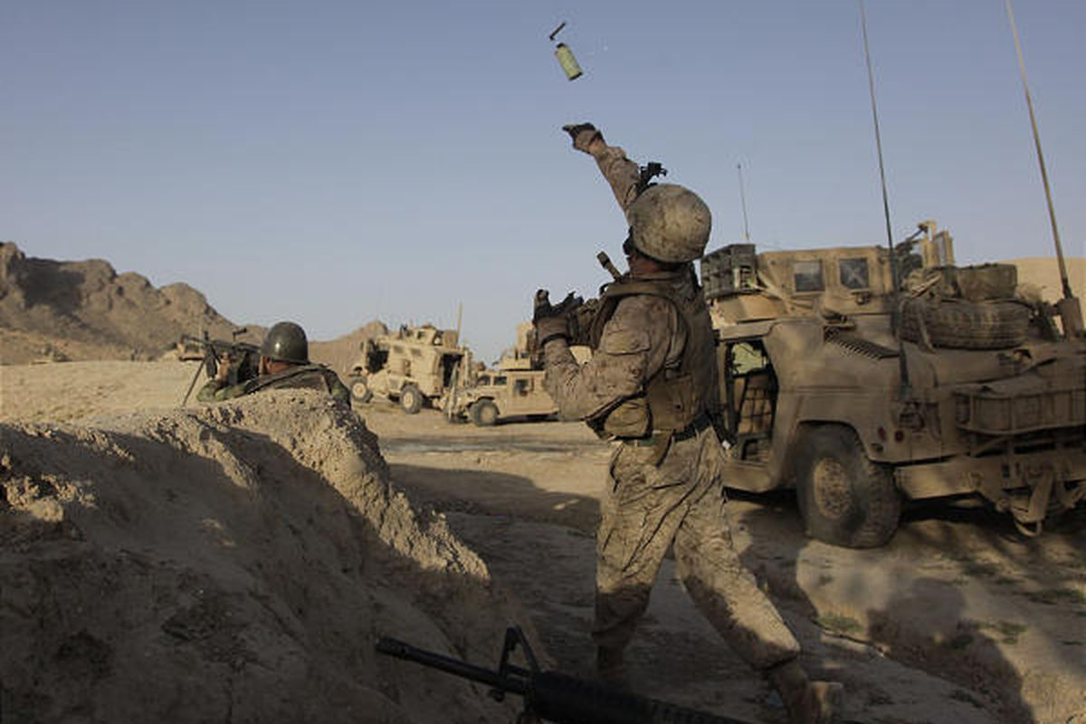 Marine Lt. Joe Cull throws a smoke grenade to provide cover in Dahaneh, Wednesday.