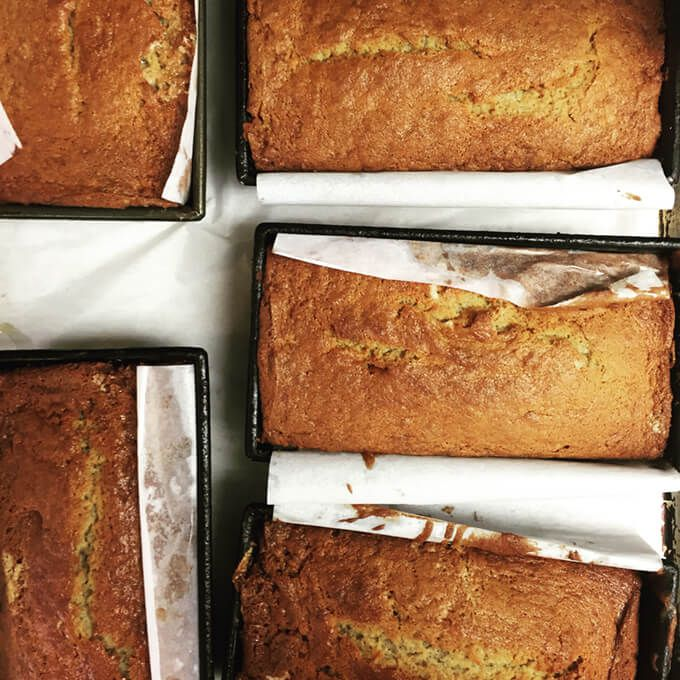 Five tins of banana bread, lined with parchment paper