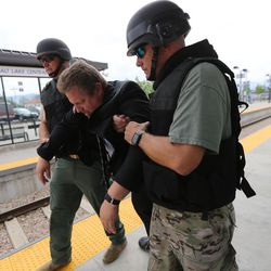 """Members of a bomb squad assist a """"victim"""" off a train during """"Hell on Wheels,"""" a full-scale, two-day, emergency protection and response drill at the Salt Lake Central Station on Tuesday, Aug. 8, 2017. The drill included emergency personnel from the Utah Transit Authority, the FBI, Salt Lake County Emergency Management, the West Valley and Salt Lake City fire departments, University of Utah Emergency Management, the University of Utah Police Department, Amtrak, Union Pacific, Murray Victim Advocates and Utah State Medical Examiner's Office. The drill simulated multiple terrorists entering the Salt Lake Valley and dividing up."""