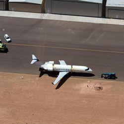 A SkyWest regional jet sits on the tarmac on the opposite end of the St. George Municipal Airport Tuesday, July 17, 2012.  A SkyWest Airlines employee wanted in a murder case attempted to steal a passenger plane, then shot himself in the head after crashing the aircraft in a nearby parking lot, officials said Tuesday. Brian Hedglin, 40, scaled a razor wire fence at the St. George Municipal Airport early Tuesday, then boarded the 50-passenger SkyWest jet while the airport was closed, St. George city spokesman Marc Mortenson said.