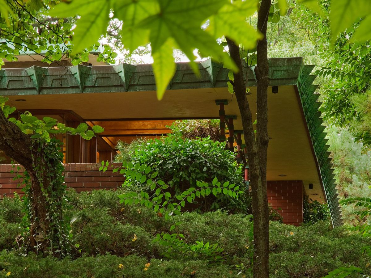 Samara by Frank Llloyd Wright. The house has a red brick exterior and a green decorated frame on the roof. The house is surrounded by trees and lush plant life.
