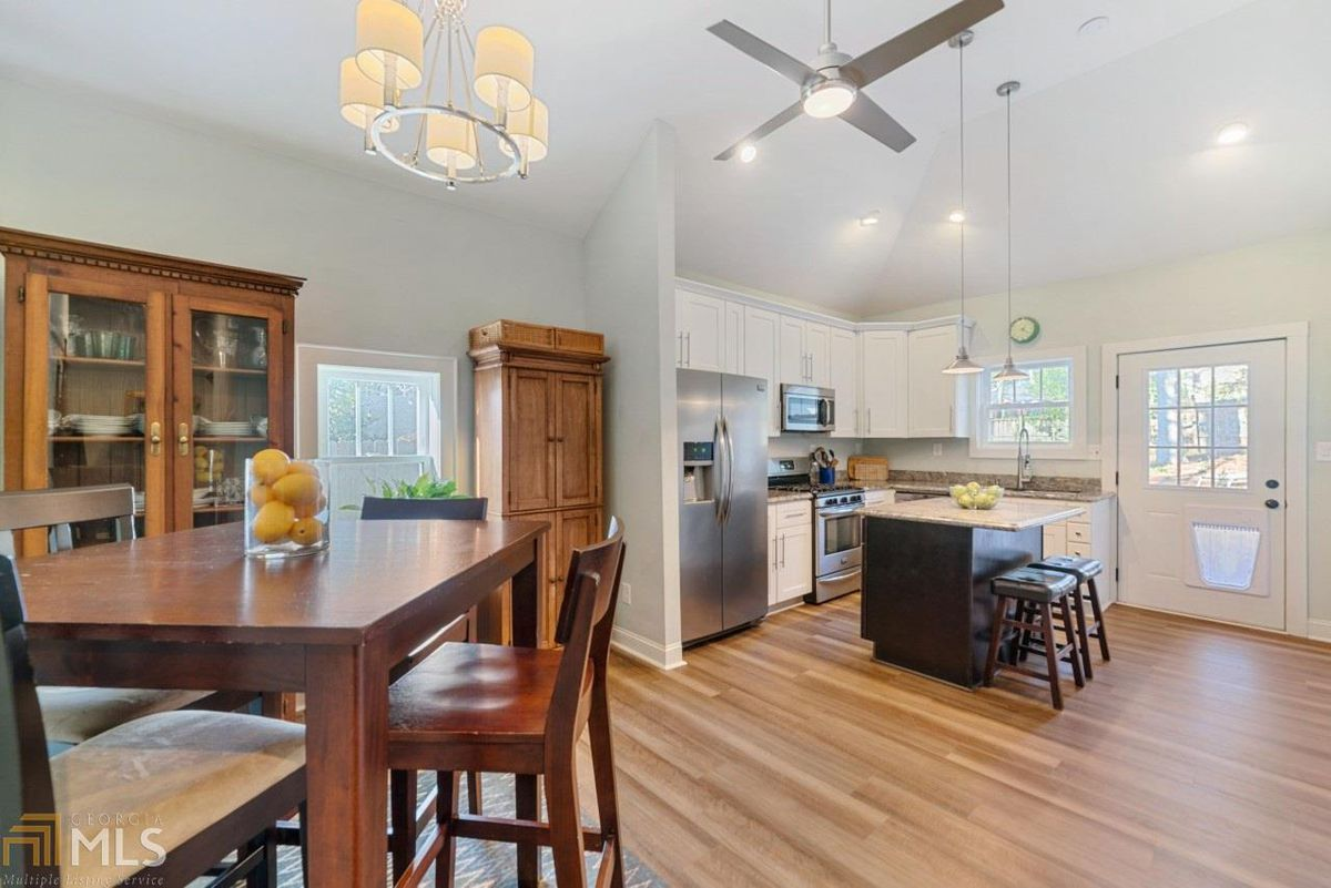 Open kitchen with dining table and chairs off to the left.