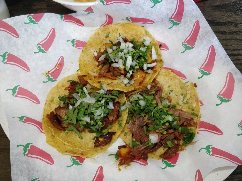 Carne asada and al pastor tacos have been topped with onions and cilantro.
