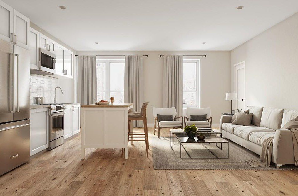 An airy living room-kitchen area with furniture and a large island delineating the two rooms.