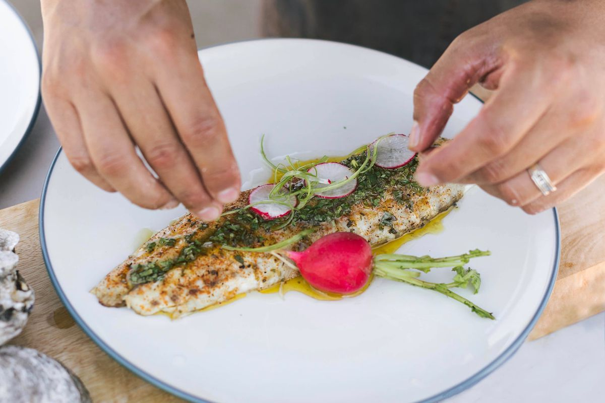 a person garnishing a dish of fish with sliced radishes and other toppings
