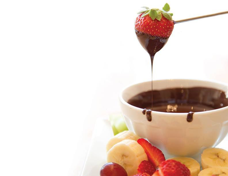 A strawberry dipped in chocolate is held over a chocolate fondue dish.