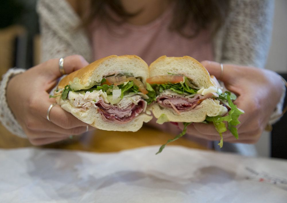 a sandwich sliced in half with several types of meat, lettuce, and tomato