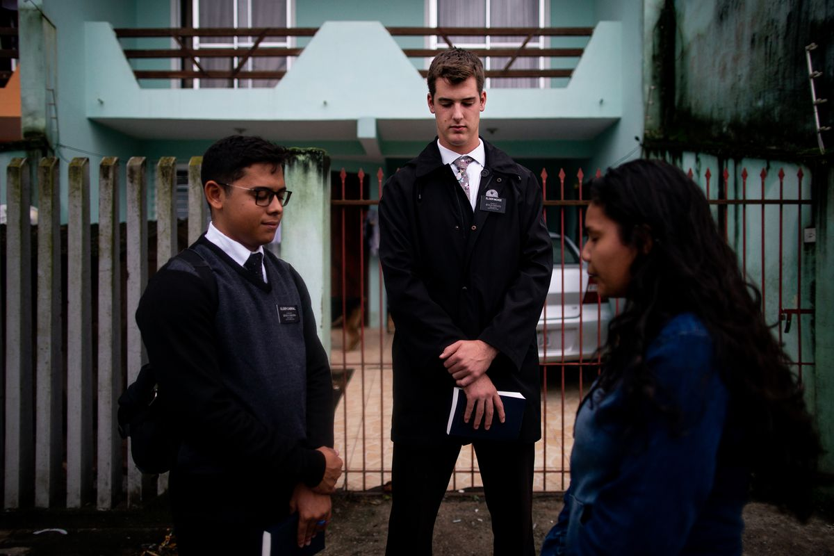 Elders Pedro Cabral and Tanner McKee, missionaries for The Church of Jesus Christ of Latter-day Saints, pray with Leandra Maia, 14, outside her home in Paranaguá, Brazil, on Sunday, June 2, 2019.