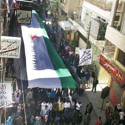 In this image provided by the Local Coordination Committees in Syria and accessed on Friday, April 13, 2012, anti-regime protesters carry a large Syrian revolutionary flag during a demonstration in Damascus, Syria.  Syrian troops shelled residential neighborhoods dominated by rebels in the central city of Homs Sunday, activists said, hours before the first batch of United Nations observers were to arrive in Damascus to shore up a shaky truce.