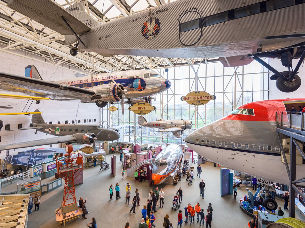 The interior of the National Air and Space Museum. There are various aircrafts and spacecrafts on display in a large room with many windows and a skylight.