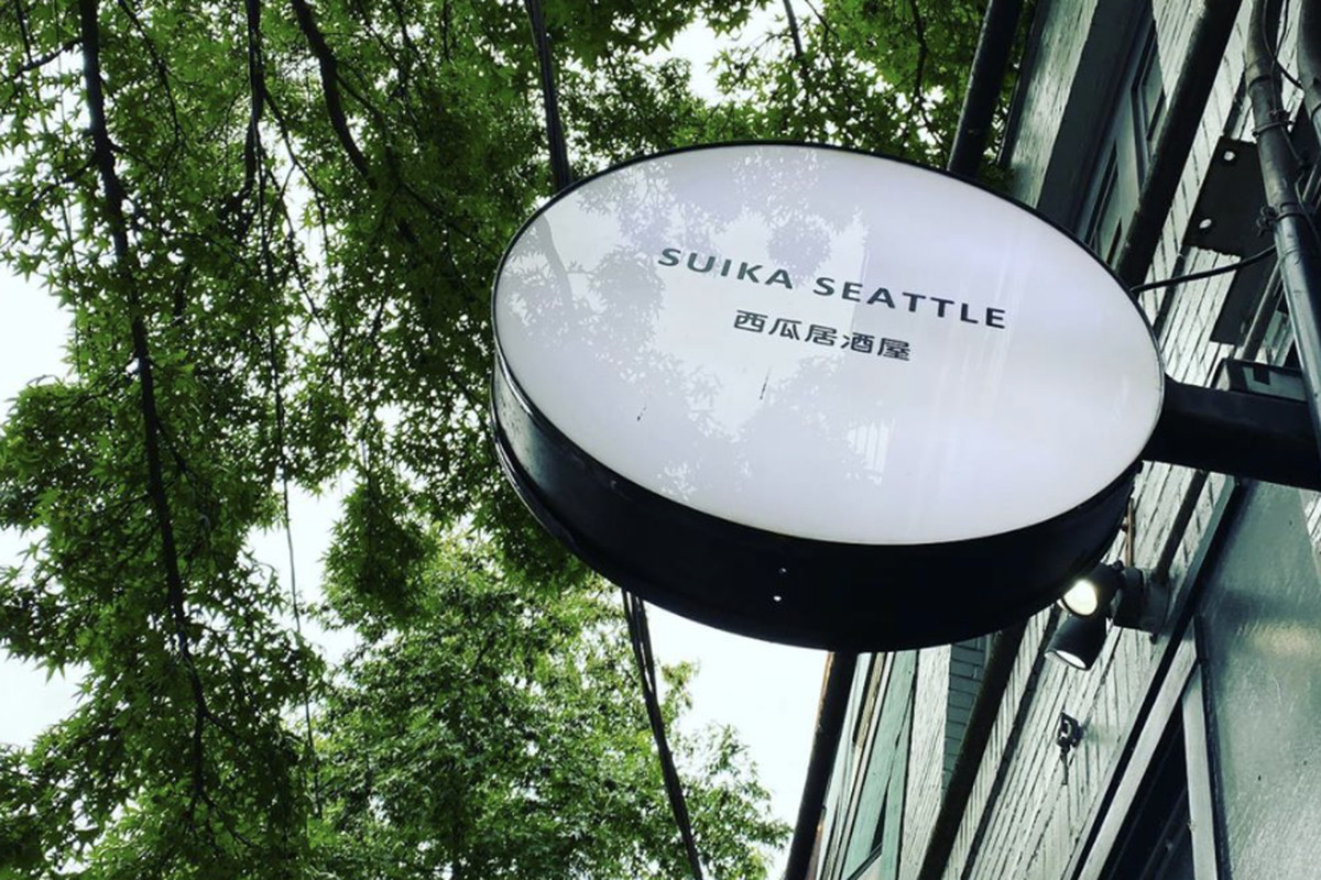 The round sign outside Suika in Seattle, with Japanese letter (and Suika's name in English) against a backdrop of leafy green trees