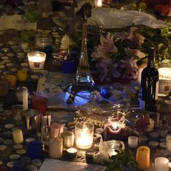 Mourners lit candles and left flowers, fruit, and wine in front of the restaurant