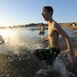 Casey McKinnon runs into the water on a frigid morning at sunrise on Lone Rock Beach at Lake Powell on Saturday, March 27, 2021. McKinnon, a 16-year-old from Benjamin, Utah County, is hearing impaired and part of the Utah Schools for the Deaf and the Blind's Yacht Club, which is training for the SEVENTY48, a 70-mile human-powered boat race from Tacoma to Port Townsend, Wash. Members of the yacht club built their boat for the race by hand.