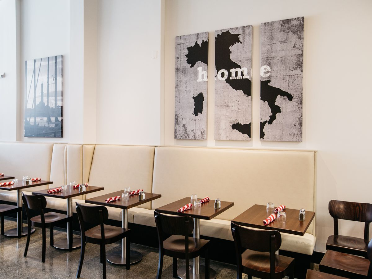 A dining room with white upholstered banquettes, two top tables, and black chairs with Italy-themed wall art.