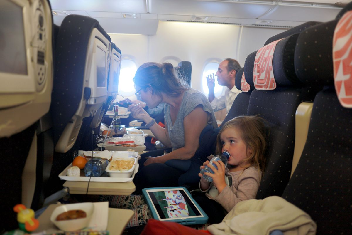 A mother and daughter during meal time on a flight from Paris to New York