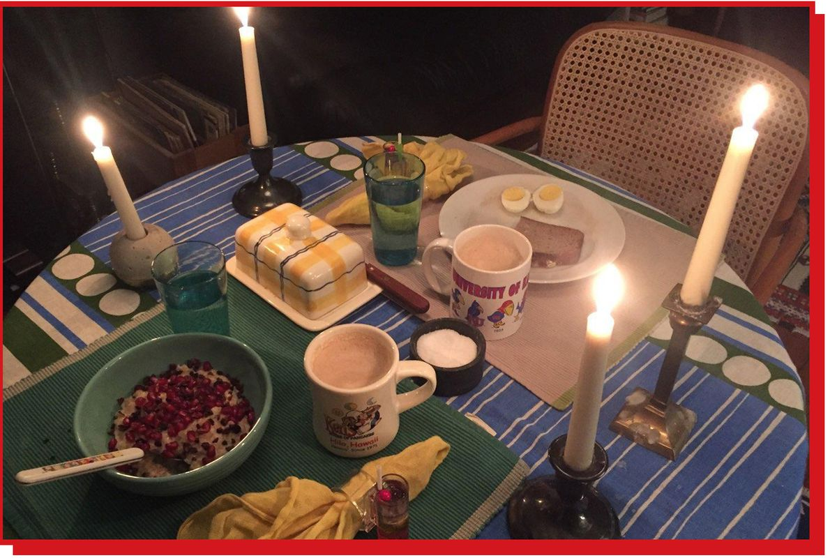 Breakfast table with four lit candlesticks alongside plates, mugs, and assorted dishes.