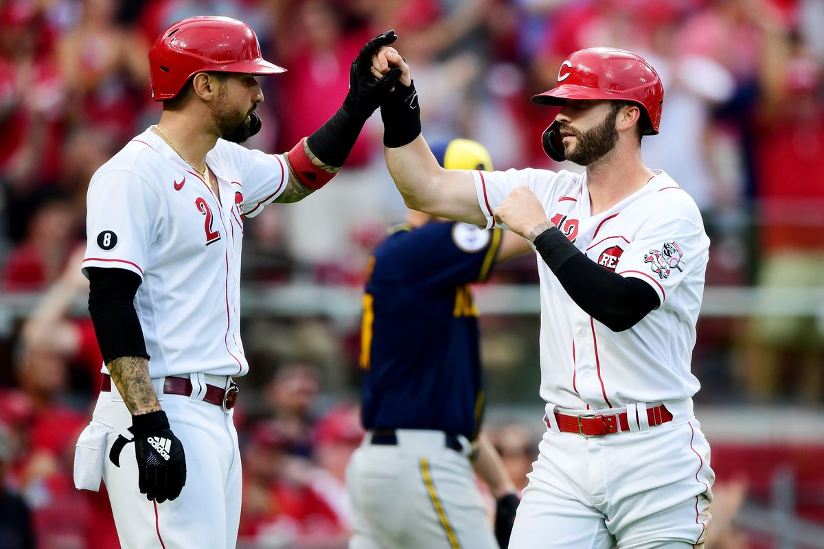 Tyler Naquin #12 celebrates with Nick Castellanos #2 of the Cincinnati Reds after being batted in during a game between the Milwaukee Brewers and Cincinnati Reds at Great American Ball Park on July 16, 2021 in Cincinnati, Ohio.