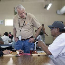 Dennis Kelsch, longtime employee of Catholic Community Services, speaks with Richard Clark, left, and a man who wished to remain anonymous at St. Vincent de Paul dining hall in Salt Lake City on Wednesday, May 31, 2017.