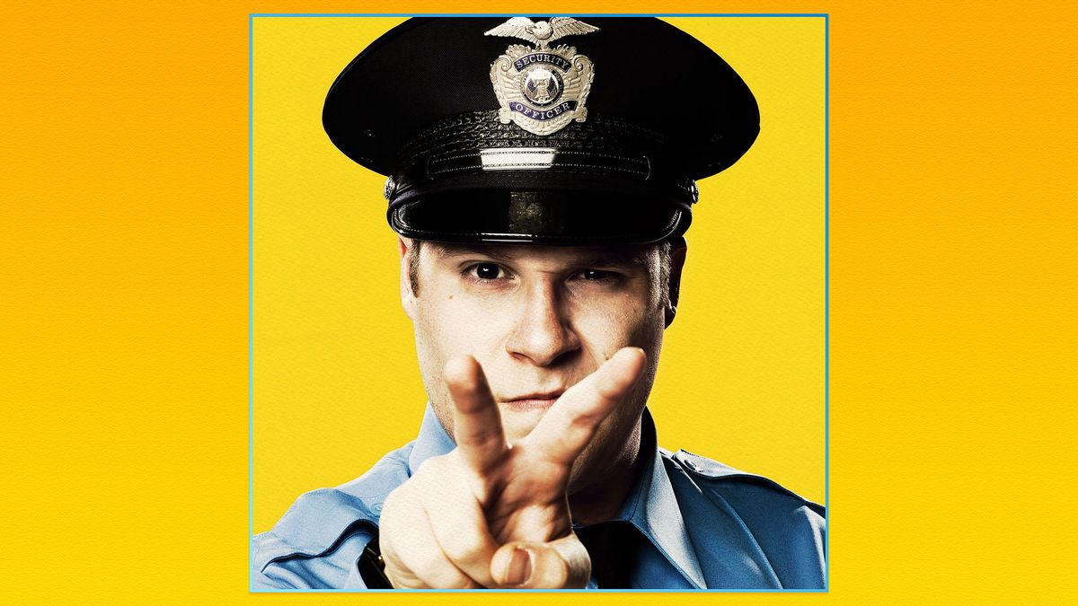 Actor Seth Rogan dressed as a security guard points two fingers towards camera on a yellow background