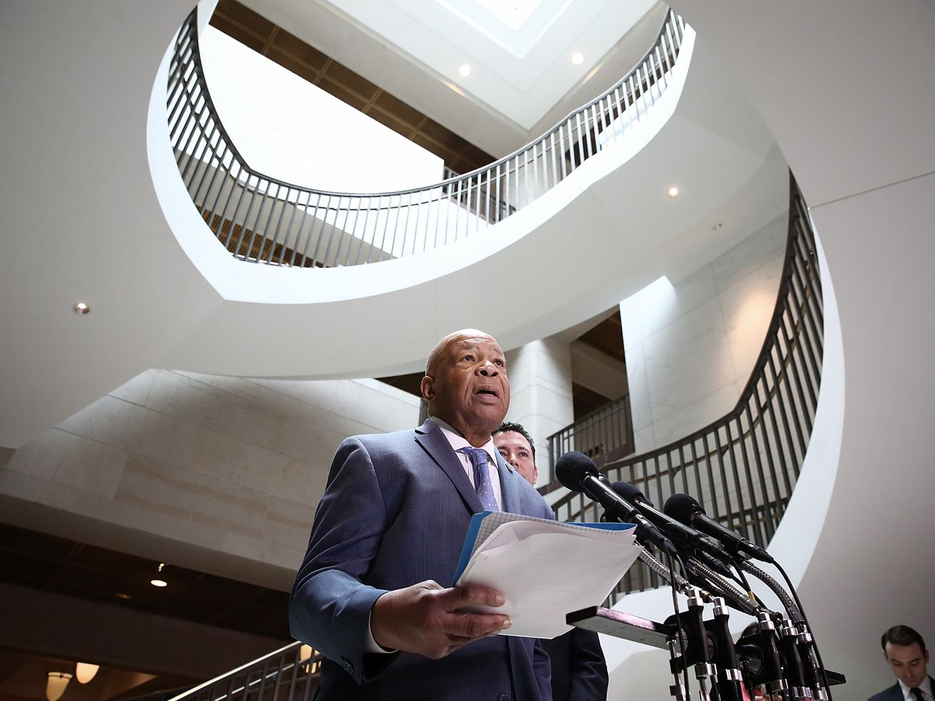 Rep. Elijah Cummings stands in front of microphones beneath a staircase in the Capitol.