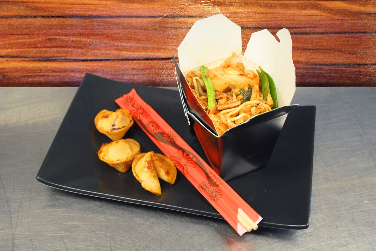 A lo mein-style dish in a Chinese takeout container is accompanied by fortune cookies