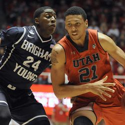 Utah Utes forward Jordan Loveridge (21) works his way to the basket as Brigham Young Cougars guard Frank Bartley IV (24) defends during a game at the Jon M. Huntsman Center on Saturday, Dec. 14, 2013.