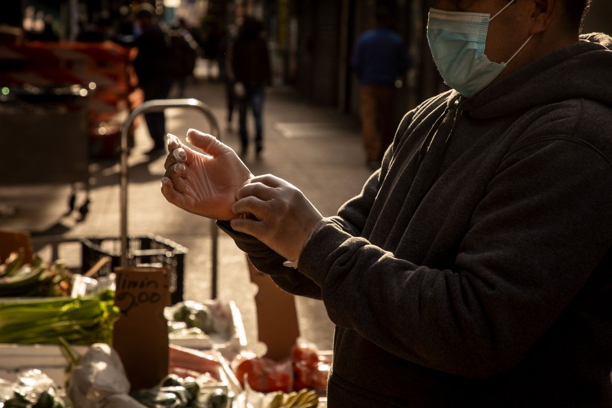 A street vendor puts on protective gloves