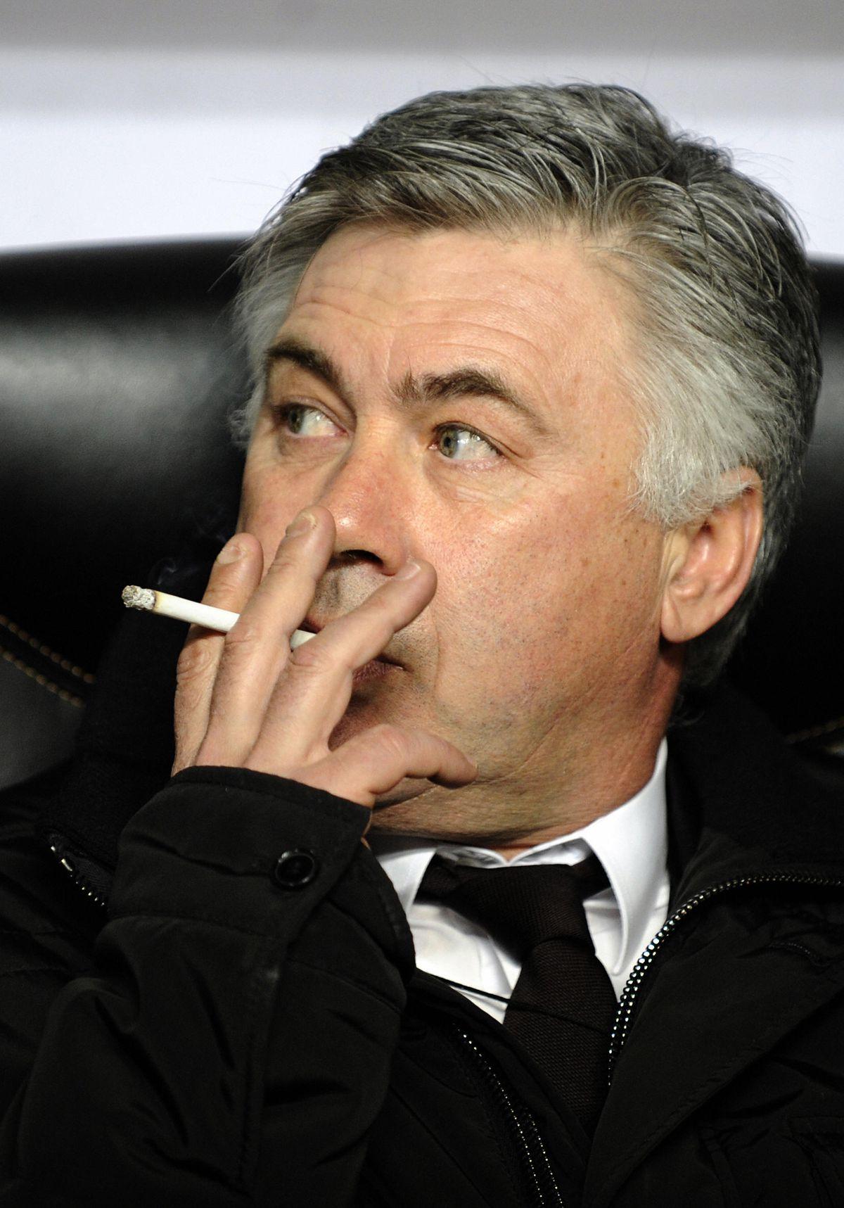 AC Milan's coach Carlo Ancelotti smokes
