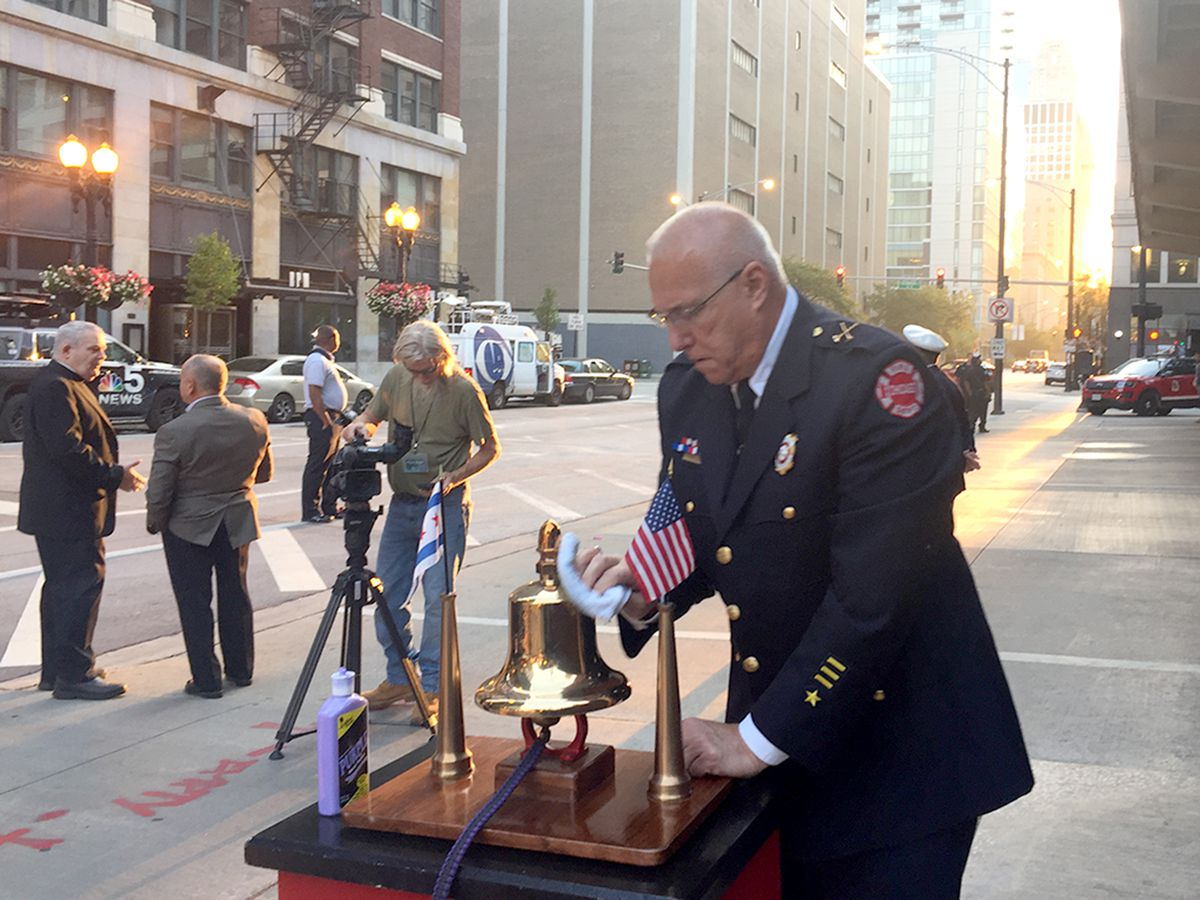 Chicago Fire Department Battalion Chief Jake Jakubec polishes the ceremonial bell in preparation for a commemoration of the 18th anniversary of the Sept. 11 attacks. The bell will be rung in four sets of five — the New York Fire Department code for a line