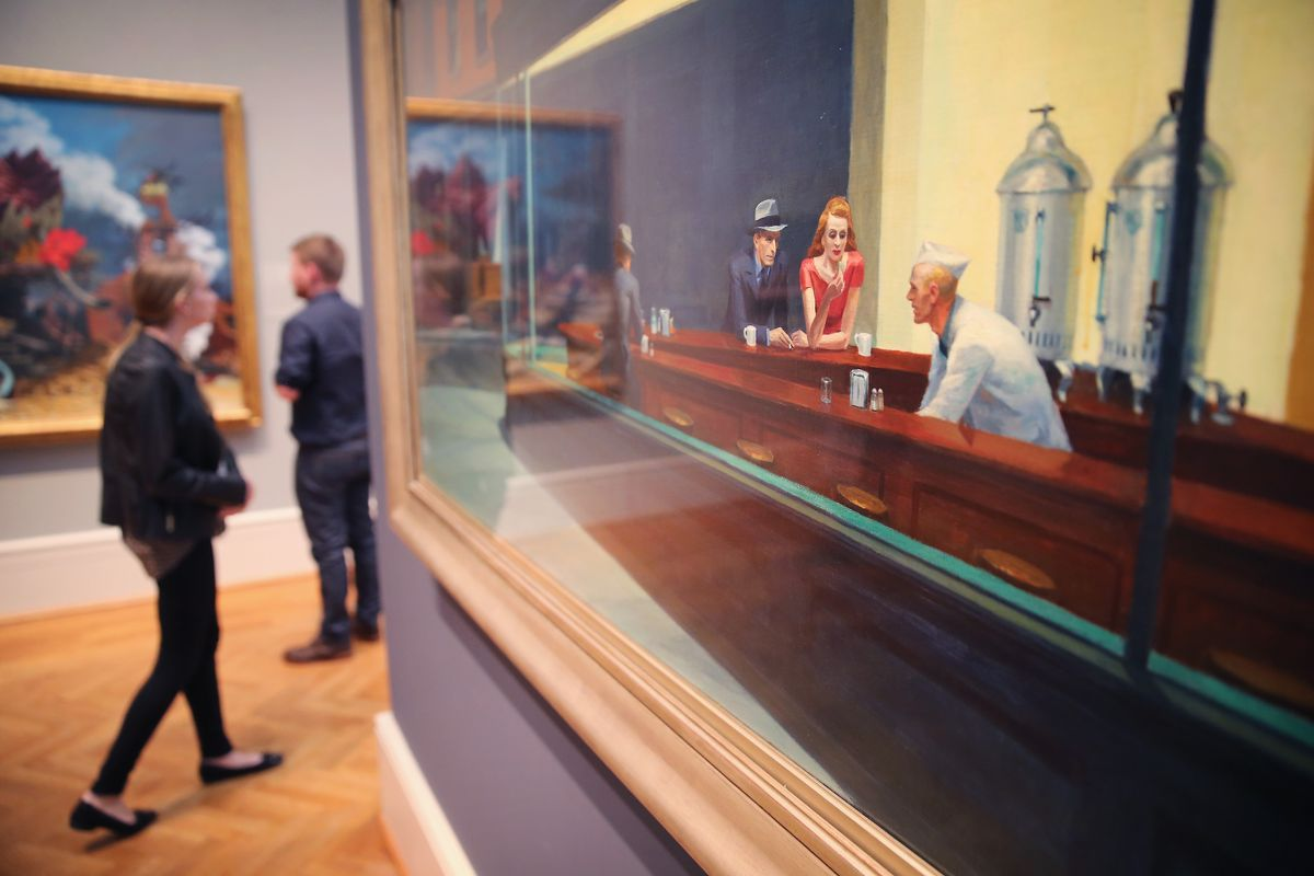 """Edward Hopper's """"Nighthawks Hangs"""" at the Art Institute of Chicago. People are walking by and admiring other paintings on the wall."""